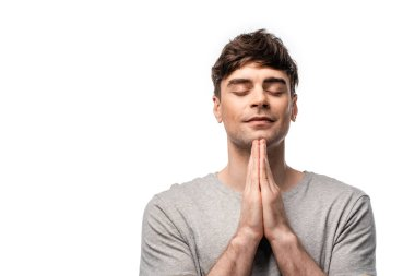 pensive man with closed eyes showing pray gesture and smiling isolated on white
