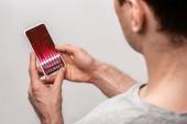 oříznutý pohled na člověka pomocí telefonu Smartphone s obchodními kurzy, izolované na šedé