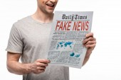 Fotografie partial view of young smiling man reading newspaper with fake news isolated on white