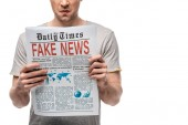 cropped view of displeased man reading newspaper with fake news isolated on white