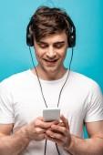 vidám fiatalember hallgat zenét fejhallgató használata közben okostelefon elszigetelt kék