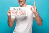 Fotografie oříznutý pohled muže zobrazující nápis ok při zobrazování novin s falešnými zprávami na modrém pozadí