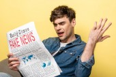 displeased young man sitting in armchair and reading fake news on yellow background