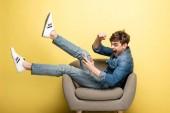 aufgeregter junger Mann zeigt Ja-Geste, während er im Sessel sitzt und das Smartphone auf gelbem Hintergrund benutzt