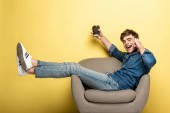 glücklicher Mann, der im Sessel sitzt, während er mit dem Smartphone spricht und Papierbecher auf gelbem Hintergrund hält