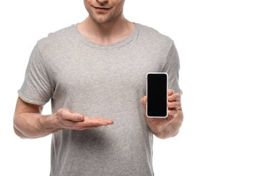 partial view of man in grey t-shirt showing smartphone with blank screen isolated on white