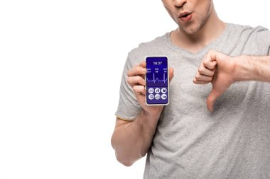 cropped view of man showing thumb down and smartphone with health app, isolated on white