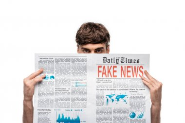young man looking at camera while holding newspaper with gake news isolated on white