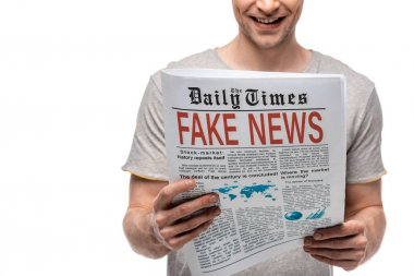 cropped view of young man reading newspaper with fake news isolated on white