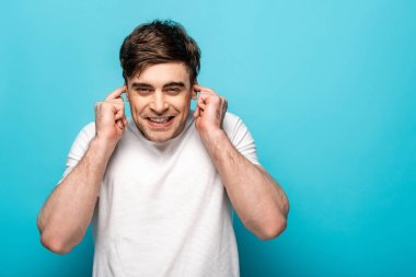 positive young man plugging ears with fingers on blue background