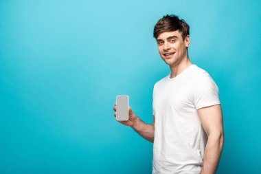 Handsome young man showing smartphone with blank screen and smiling at camera on blue background stock vector