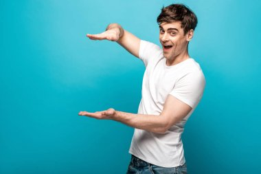 cheerful young man showing size gesture while smiling at camera on blue background