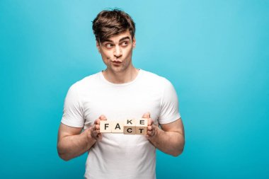 discouraged young man holding wooden cubes with fake fact lettering on blue background