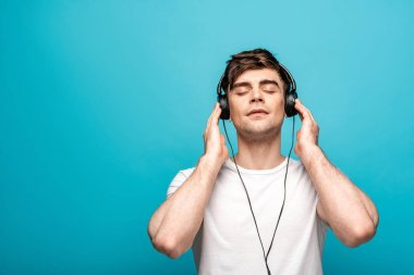 dreamy young man in headphones listening music with closed eyes on blue background