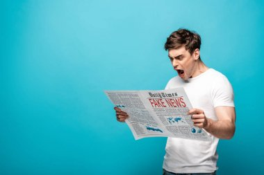 angry young man reading newspaper with fake news on blue background