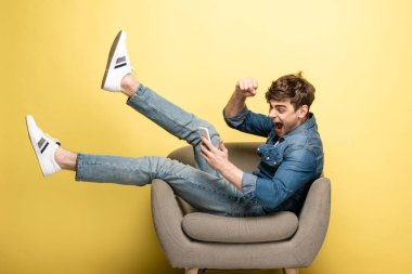 excited young man showing yes gesture while sitting in armchair and using smartphone on yellow background
