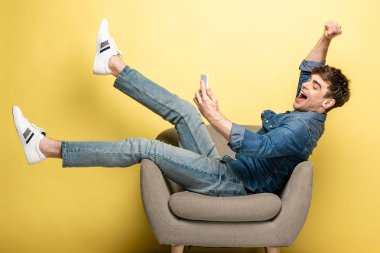 happy man using smartphone while sitting in armchair and showing winner gesture on yellow background