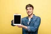 Veselý pohledný muž zobrazující digitální tablet s prázdnou obrazovkou na žlutém pozadí