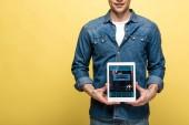 vágott kilátás az ember denim ruhát gazdaság digitális tabletta a foglalás app, elszigetelt sárga