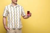 oříznutý pohled na usmívající se muž zobrazující smartphone s obchodními kurzy, izolovaný na žlutém