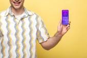 oříznutý pohled na usmívající se muž zobrazující smartphone s nákupní aplikací, izolovaný na žlutém