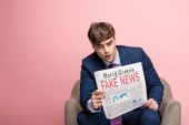 Fotografie serious businessman sitting in armchair and reading newspaper with fake news on pink background