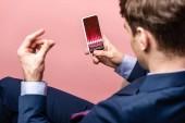 Fotografie ostříhané zobrazení obchodníka pomocí telefonu Smartphone s obchodními kurzy, izolované na růžovém