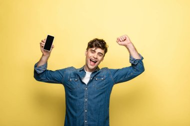 cheerful young man holding smartphone with blank screen and showing winner gesture on yellow background