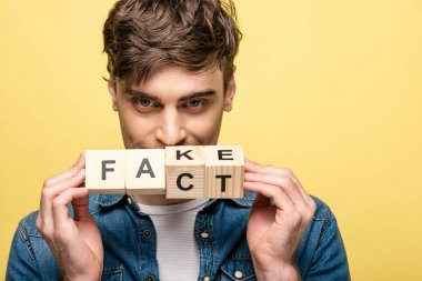positive young man looking at camera while showing wooden cubes with fake fact lettering  on yellow background