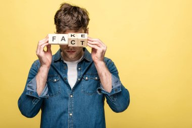 young man in denim shirt showing wooden cubes with fake fact lettering on yellow background