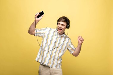 cheerful young man dancing while listening music with headphones and smartphone on yellow background