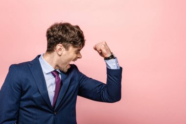 angry businessman showing fist and screaming on pink background