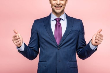 Cropped view of smiling businessman showing thumbs up on pink background stock vector