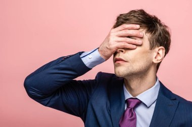 upset businessman covering eyes with hand isolated on pink
