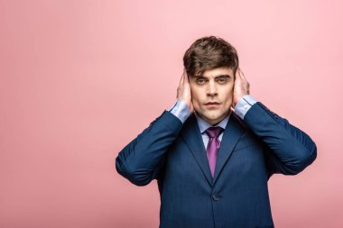 confident businessman covering ears wit hands isolated on pink