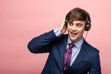 cheerful businessman listening music in earphones while looking away on pink background