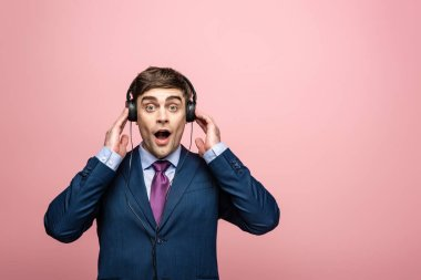 surprised businessman looking at camera while listening music in earphones isolated on pink