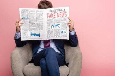businessman sitting in armchair and reading newspaper with fake news on pink background