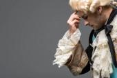 Seitenansicht der nachdenklichen viktorianischen Gentleman in Perücke denken isoliert auf grau