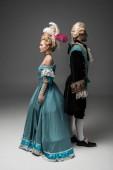 aristokratická žena a muž ve viktoriánském oblečení, stojící zpátky na záda