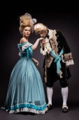 handsome victorian man kissing hand of woman in wig while standing on black