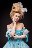 beautiful young victorian woman in wig standing in blue dress on black