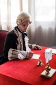 selektivní zaměření pohledného viktoriánského muže v paruce držící peří a psaní dopisu