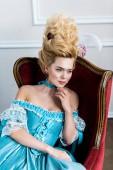 fiatal viktoriánus nő kék ruhában ül antik szék