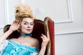 vidám viktoriánus nő kék ruhában ül antik szék