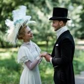 Veselý viktoriánský muž a žena v kloboucích, kteří se drželi za ruce, zatímco stáli venku