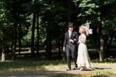 šťastná mladá viktoriánská žena a pohledný muž s kloboukem venku