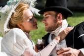 pohledný aristokratický muž blízko atraktivní viktoriánské ženy v klobouku