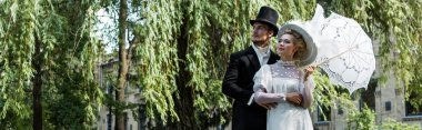 panoramic shot of handsome victorian man standing with woman holding umbrella