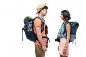 two young, smiling tourists with backpacks looking at each other isolated on white